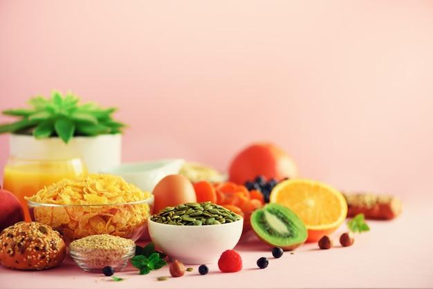 Breakfast served with soft boiled egg, oat flakes, nuts, fruits, berries, milk, yogurt, orange, banana, peach on pink background.