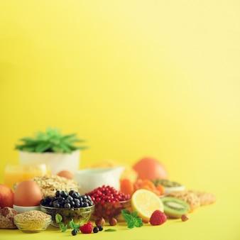 Breakfast served with soft boiled egg, oat flakes, nuts, fruits, berries, milk, yogurt, orange, banana