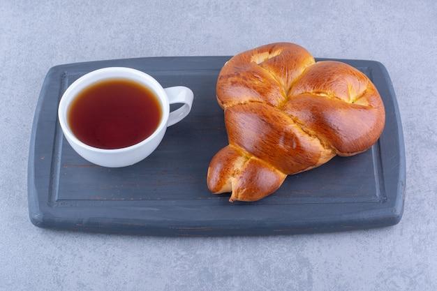 La colazione che serve di tè e panino dolce su una tavola su una superficie di marmo