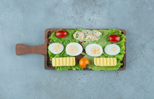 Breakfast serving with vegetables, boiled eggs, butter and a salad serving, on marble background. high quality photo