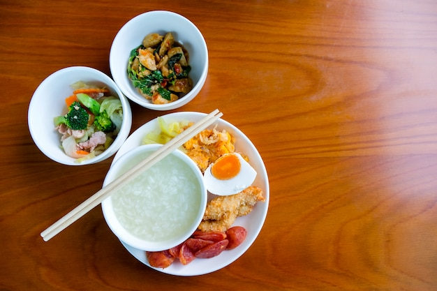 Breakfast set, boiled rice in a bowl, stir-fried vegetables, fried meatballs with basil
