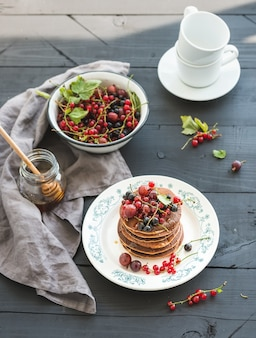 Breakfast set. buckwheat pancakes with fresh berries and honey on rustic plate over black wooden table.