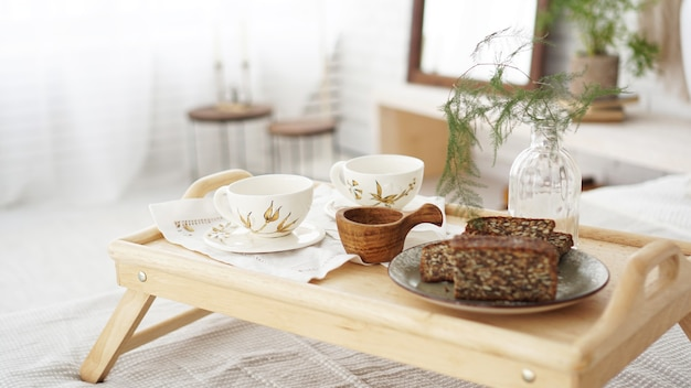 Breakfast set close up in the room. cups on a tray with vase on the bed. selective focus. scandinavian style.