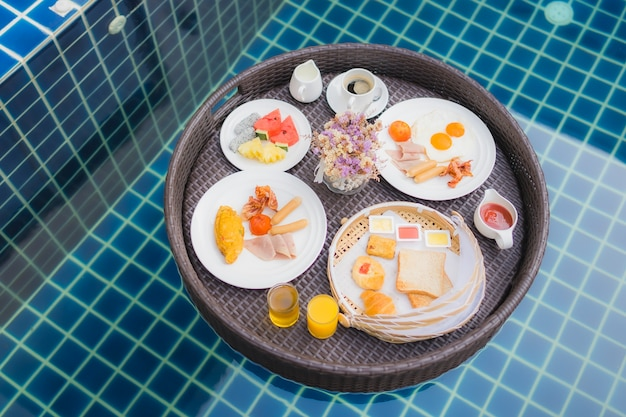 Breakfast set floating around swimming pool