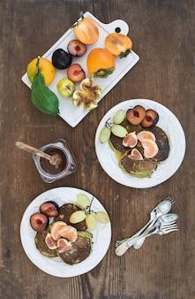 朝食セット。素朴な木製の上の白いセラミックプレートに新鮮な梅、タンジェリン、ブドウ、イチジク、蜂蜜と自家製ズッキーニのパンケーキ。