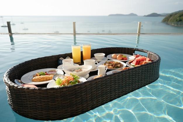 Завтрак на подносе в бассейне, плавучий завтрак на тропической вилле курорта с видом на океан.