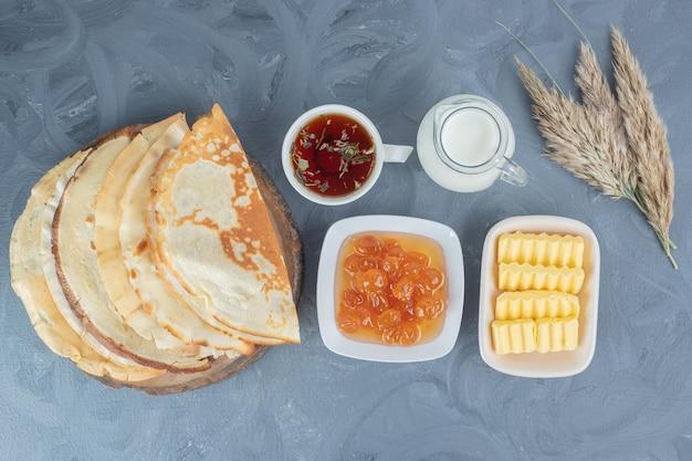 Набор для завтрака блины, варенье из белой вишни, масло, чашка чая и молоко на мраморной поверхности.