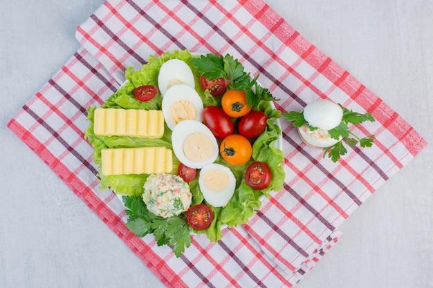 大理石のテーブルの上のタオルの大皿に野菜、ゆで卵、バタースライスの朝食セット。