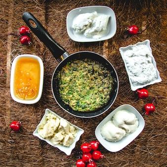 Набор для завтрака омлет с зеленью, сыром, медом, сливочным сыром и маслом сверху.