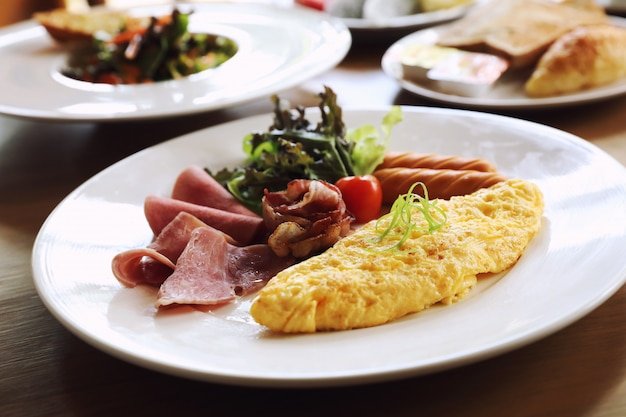 Breakfast set omelette with sausage bacon and salad on wood