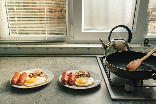 Breakfast set of sausages fried eggs and mushroom on the kitchen counter in warm morning light.