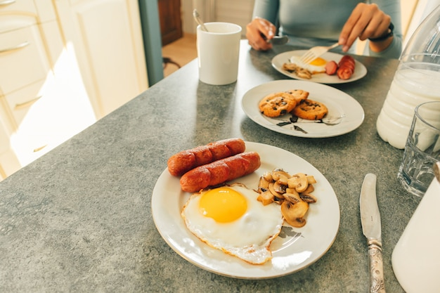 Breakfast set of sausages fried eggs and mushroom with fresh milk and cookies served on the table.