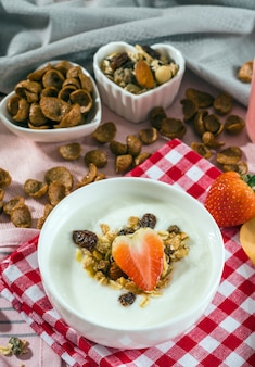 Breakfast set. Strawberry fruit over the yogurt in white bowl with Oat granola and nuts on table set
