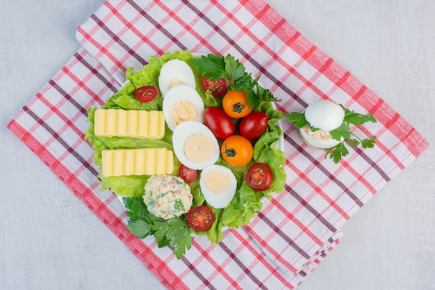 Breakfast set of vegetables, boiled eggs and butter slices on a platter on a towel on marble table.