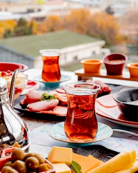 Breakfast set with tea sliced cheese olives and sausages