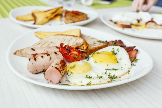Breakfast setting with fried eggs, bacon, muesli, croissants and juice