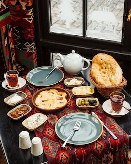 Сервировка на завтрак с яйцом и колбасой, фиговое варенье, оливковое масло, сыр и чай