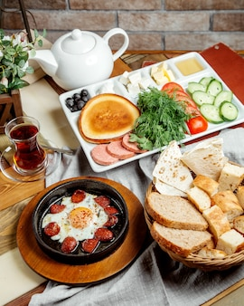 Breakfast setup with egg and sausage dish breads vegetable slices cheese honey and tea