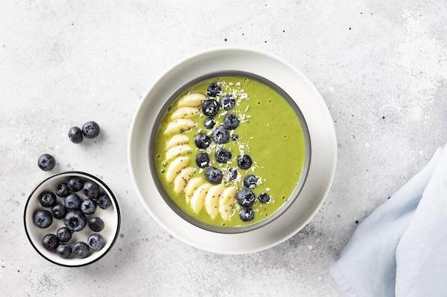緑の抹茶、バナナ、アーモンドミルク、ブルーベリーの朝食スムージーボウル。健康的な食事