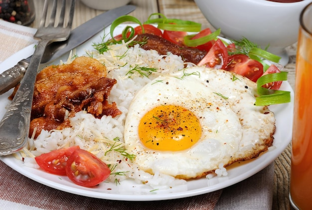 Breakfast - soft boiled rice with scrambled eggs, bacon, tomato slices and greens