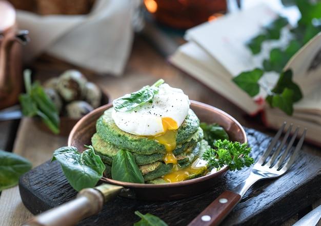木製のテーブルに半熟卵と朝食ほうれん草のパンケーキ