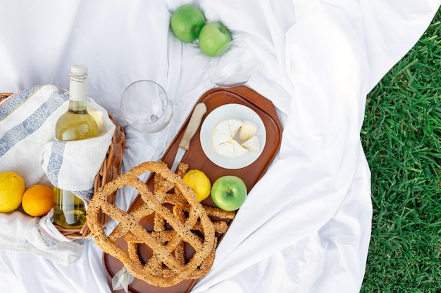 Breakfast at sunrise, on the grass white sheet with a tray with cheese and vine, dry bread, apple, lemon. romantic mood, slow lifestyle aestetic concept, top view