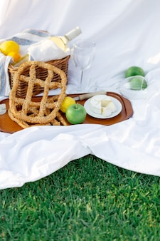 Breakfast at sunrise, on the grass white sheet with a tray with cheese and vine, dry bread, apple, lemon. romantic mood, slow lifestyle aesthetic concept, top view