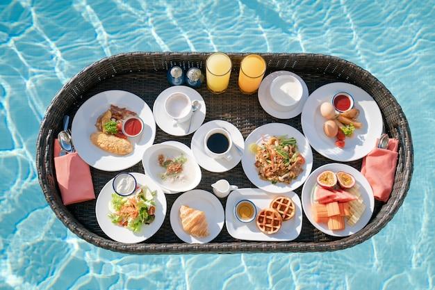 Breakfast in swimming pool, floating breakfast set in tray in resort.