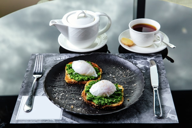 Breakfast table setting, toasted bread with poached egg and greens