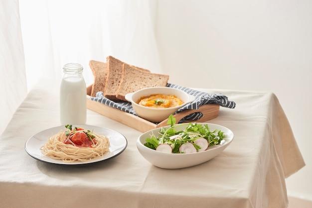 朝食用テーブル;大根とカボチャのピューレ、パン、ミルクをテーブルに置いたサラダを添えたスパゲッティ