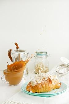 朝食のテーブル。クロワッサンにコーヒーのしぶきと落下アーモンドフレーク。飛行食品のコンセプト。コピースペース