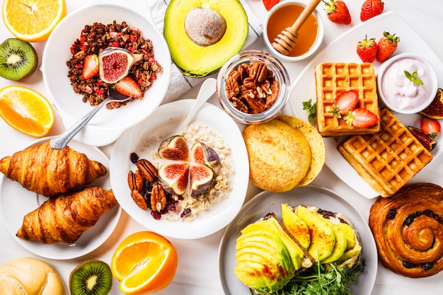 Breakfast table with avocado toast, oatmeal, waffles, croissants on white