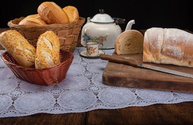素朴な木の上のレースのテーブルクロス、選択的な焦点で、パン、ティーポット、コーヒー、ナイフの朝食用テーブル。