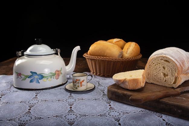 レースのテーブルクロスと素朴な木材にパン、ティーポット、コーヒーカップ、ナイフを備えた朝食用テーブル。