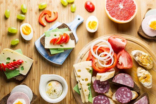 チーズサンドイッチ、ソーセージ、野菜、ゆで卵、果物の朝食用のテーブル。上面図