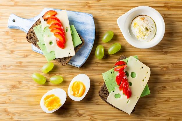チーズサンドイッチ、野菜、ゆで卵、果物の朝食用のテーブル。上面図