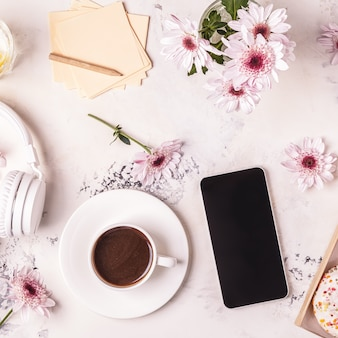 Breakfast table with coffee, phone and headphones with beautiful flowers