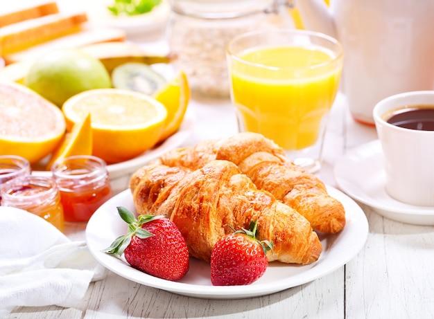 Стол для завтрака с круассанами, кофе, апельсиновым соком, тостами и фруктами