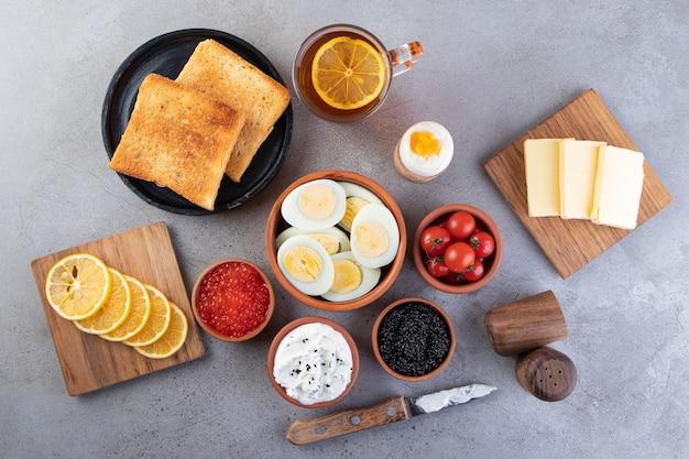 Tavolo per la colazione con una tazza di tè e uova sode sul tavolo di pietra.