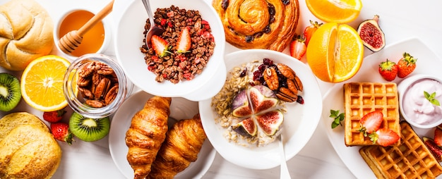 Breakfast table with oatmeal, waffles, croissants and fruits.