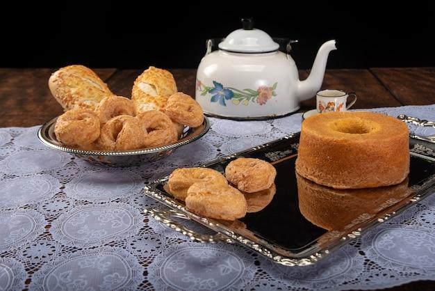 甘いドーナツ、パン、ケーキ、ティーポット、コーヒー1杯の朝食用テーブルと、レースのテーブルクロスと素朴な木のトレイ、厳選されたフォーカス。