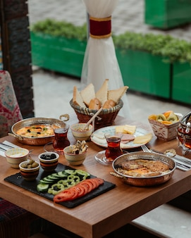 Breakfast table with variety of foods, cheese, vegetables, omlettes, sausages, honey and olives.