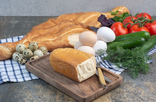 Breakfast table with vegetables, bread, eggs and cheese.