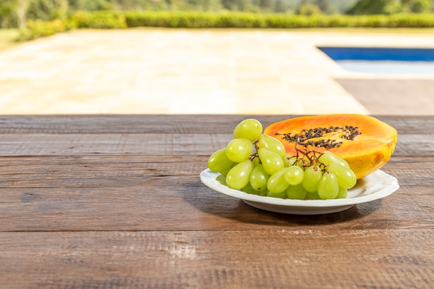 Breakfast table, with white plate with papaya and grape. pool