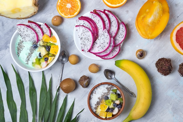 Breakfast table with yogurt acai bowls and fresh tropic fruits on a gray stone background with palm leaves, flat lay