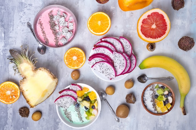 Breakfast table with yogurt strawberry smoothie bowls and fresh tropic fruits on a gray stone background. acai bowl of wild berry and fruits smoothie bowl, flat lay