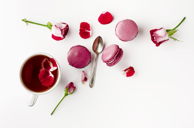 Breakfast tea on white table with roses and macarons