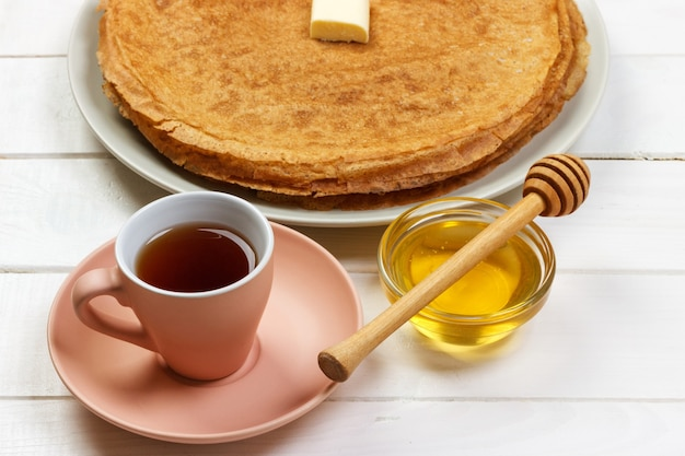 Breakfast tea with pancakes and honey on wooden surface.