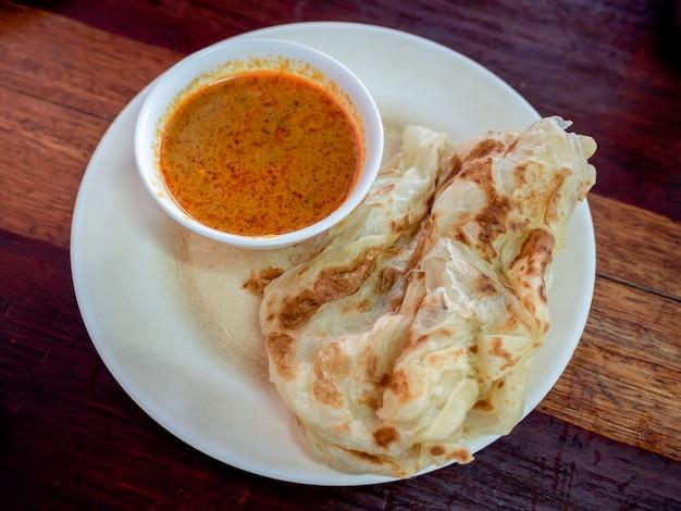 朝食タイ南部スタイル。木製のテーブルの白い皿にココナッツミルクカレーのロティ。