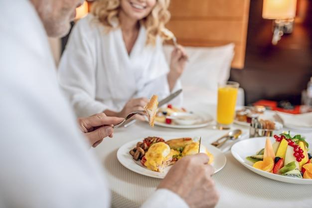 아침 식사 시간. 아침을 먹고 기뻐하는 흰 가운을 입은 부부